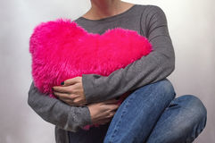 Girl hugging pillow heart crimson Royalty Free Stock Photography