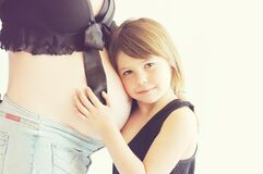 Girl hugging pregnant mother's belly Stock Photo