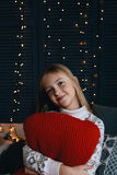 Girl hugging red pillow on winter day Royalty Free Stock Photo