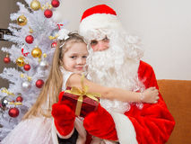 Girl hugging Santa Claus which is holding a gift Stock Photo