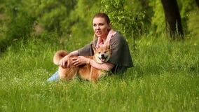 Girl hugging and talking to dog Shiba Inu stock video