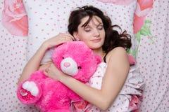 Girl hugging teddy bear in a dream Royalty Free Stock Photos