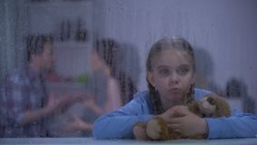 Girl hugging teddy bear on rainy day, father choking mother on background. Stock footage stock video