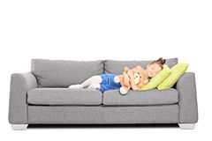Girl hugging a teddy bear and sleeping on couch Royalty Free Stock Image