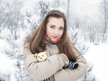 Girl hugging toy dog with cold trees on the back Stock Images