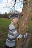 Girl Hugging Tree. Girl dressed for the cold hugging the trunk of a tree Stock Photos
