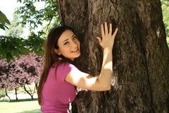 Girl hugging tree in garden Royalty Free Stock Images