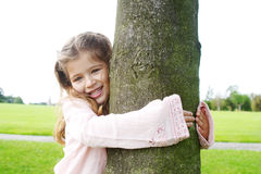 Girl hugging tree in park. Stock Image