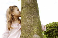 Girl hugging tree in park. Royalty Free Stock Images