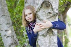 Girl hugging tree trunk Royalty Free Stock Image