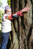 Girl hugging tree trunk Royalty Free Stock Images