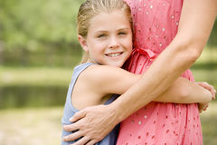 girl hugging woman around the waist Stock Photo