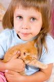 Girl hugs ginger kitten Stock Image