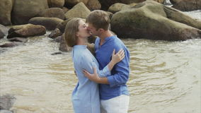 A girl hugs a guy on the ocean against a background of large stones. Couple Kissing On The Sea.  stock footage