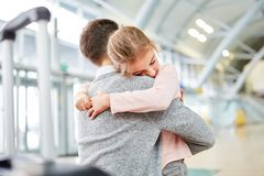Girl hugs her father in the airport terminal royalty free stock photos