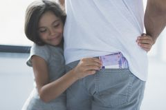 The girl hugs her father, smiles cunningly and looks at the money that he tries to steal from his back pocket. A little cunning. A little girl hugs her father stock image