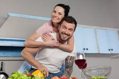 The girl hugs her husband in the kitchen, they cook and fool, they are happy together stock photo