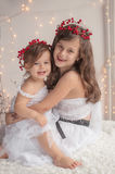 Girl hugs her little sister, both wearing red Christmas caps and Royalty Free Stock Photography