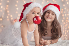 Girl hugs her little sister, both wearing red Christmas caps and Royalty Free Stock Image