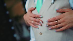 The girl hugs her young man standing behind him. Close-up of her hands. stock footage