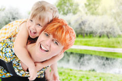 Girl hugs her young mother in the park Stock Photos