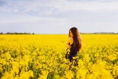 Girl hugs herself on rapeseed meadow Royalty Free Stock Image