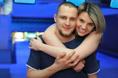 Girl hugs man and smiles in bowling of club Royalty Free Stock Photography