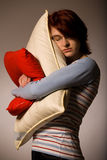 Girl hugs pillows Stock Images