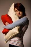 Girl hugs pillows Stock Images