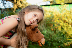 Girl hugs a rocking horse. Royalty Free Stock Images