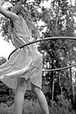 Girl with Hula Hoop. Young girl playing with hula hoop outdoors royalty free stock photos