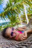 Girl in hummock on tropical beach Stock Images