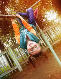 The girl hung on the bar. Portrait of a young girl hanging like monkey on the bar at the playground Stock Photos