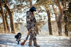 Girl hunter with binoculars in the forest, shows dog direction s stock photo