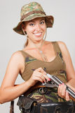 Girl hunter in camouflage, gun charges. Gray background. Royalty Free Stock Image