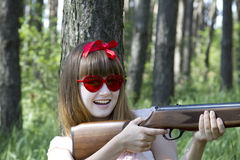 Girl hunting with rifle in the forest Royalty Free Stock Image