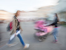Girl hurrying and women with a baby in a stroller Royalty Free Stock Photo