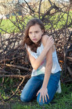 Girl hurt kneeling embracing her hand near the dry branc Royalty Free Stock Images