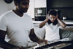 Girl Hurts From Boyfriend`s Synthesizer Play. Afro American Girl Hurt From Boyfriend`s Synthesizer Playing. Working Musician. Musical Hobby. Hands On Keyboard stock photo