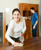 Girl with husband cleaning furniture Stock Images