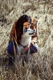Girl husky is scratching behind the ear and smiles . Royalty Free Stock Photos