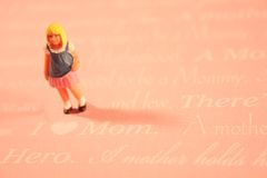 Girl: I Love Mom concept. Concept: A young girl loves her mom. A miniature figurine of a girl stands on phrases and words having to do with Mother. Background is Stock Images