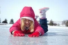 Girl On Ice. Young Girl Sliding Prone on Frozen Lake During Winter Stock Photography