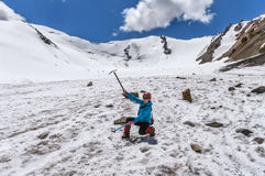 Girl with ice ax on glacier. Girl climber with two ice axes on the glacier on a sunny day in the mountains of Kyrgyzstan during a mountain hike Royalty Free Stock Photos