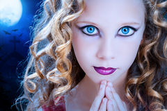 Girl with ice blue eyes at halloween. Extreme close up facial portrait of young Girl with big blue eyes. Beauty cosmetic make up on pre teen with graveyard at royalty free stock photos