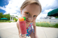 Girl with ice-cream. A cute little caucasian white girl with friendly smiling facial expression holding a pink sorbet ice-cream in her hand outdoors Royalty Free Stock Photography