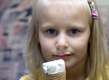 Girl and ice-cream cornet. A cute blond girl with an ice-cream cornet in her hand Stock Image