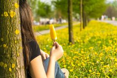 Girl with  ice cream. Girl sits leaning on a tree and eating ice cream surrounded with yellow dandelion flowers. Spring time Royalty Free Stock Images
