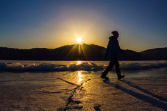 Girl is on the ice of Lake Baikal in the light of the setting su Stock Photos