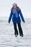 Girl on ice skates. Girl relaxing riding on ice skates, on frozen lake. Winter sports Royalty Free Stock Images